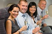 Business people flying airplane drink champagne smiling at camera