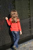 WASHINGTON, D.C. - OCT 29, 2013: Unidentified little girl looks for a name on the wall at Vietnam Ve