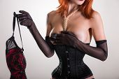image of corset  - Glamorous pinup woman in corset holding red bra - JPG