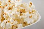 stock photo of popcorn  - closeup of popcorn in a white bowl - JPG