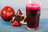stock photo of pomegranate  - Red pomegranate juice in a glass near a fruit pomegranate and half of pomegranate on blue wooden background - JPG