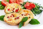 Mini quiche filled with vegetables with salad.Focus on the front pie.
