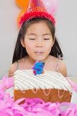 Close-up of a cute little girl blowing her birthday cake