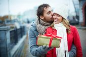 Image of affectionate guy kissing his girlfriend while giving her present outside