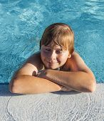Child Rest On His Elbow At The Edge Of The Pool