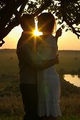 Couple kissing under tree at evening