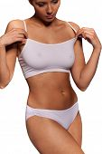 Close up view of the midriff torso of an athletic woman in a white sports bra and panties with a sha