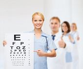 healthcare, medicine, advertisement and sale concept - smiling female doctor or nurse with stethoscope and eye chart