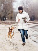 Walking together : girl with beagle dog runs along the autumnal sand beach