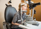 Little boy undergoing eye examination with slit lamp in store