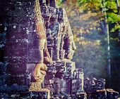 Vintage retro effect filtered hipster style travel image of Ancient stone faces of Bayon temple, Angkor, Cambodia on sunset