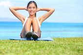 Exercise woman doing situps in outdoor workout training in grass on beach. Asian sport fitness woman