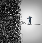 stock photo of overcoming obstacles  - Crisis Management business concept as a tightrope walker walking out of a confused tangled chaos of wires breaking free to a clear path of risk opportunity as a metaphor for managing organizational challenges for financial freedom and success - JPG