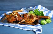 Roasted quails  on tray, on wooden table background