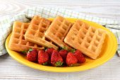 A plate of waffles and strawberries on a yellow platter. Horizontal format on a rustic wooden farmho