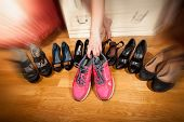 Active Woman Picking Sneakers Rather Than High Heels. Photo With Motion Blur