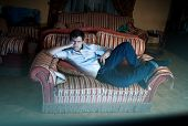 Man Lying On Sofa And Watching Tv At Night