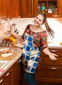 Laughing Young Housewife In Apron On Kitchen