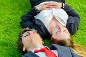 Successful Junior Executives Dynamics Lying On Grass