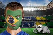 Composite image of serious young brasil fan with face paint against large football stadium with bras