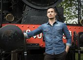 Handsome Young Man In Denim Shirt In Front Of Old Train