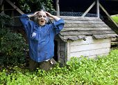 stock photo of freaky  - funny zombie in front of a dog house - JPG