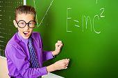 A schoolboy screams violently at the blackboard in the classroom. Education.