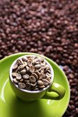 Cup full of green coffee beans on brown coffee beans background