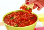 Dipping Into Salsa With A Tortilla Chip