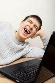 picture of hysterics  - Teenager hysterical laughing with Laptop on the Sofa - JPG