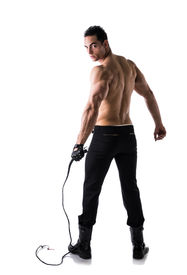 foto of strip tease  - Muscular shirtless young man with whip and studded glove full length shot from back - JPG