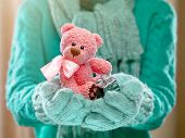Little teddy bear in female hands in cozy mittens. Woman hands in teal mittens holding a cute tiny teddy bear. Winter time and Christmas present concept.
