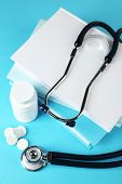 Medical stethoscope with books and tablet on blue background