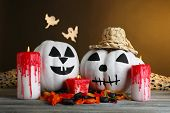 White Halloween pumpkins and candles on wooden table on dark color background