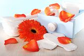 Sanitary pads in box, orange flower and rose petals on wooden table on light blue background