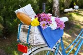 Bicycle with flowers, bread and bottle of wine in wooden box on grass background