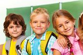 Children stand close to each other near blackboard