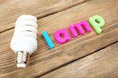 Lamp word formed with colorful letters on wooden background
