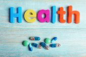 Health word formed with colorful letters on wooden background