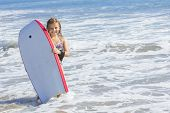 stock photo of boogie board  - Cute little girl boogie boarding in the ocean - JPG