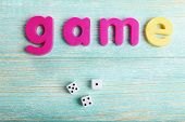 Game word formed with colorful letters on wooden background