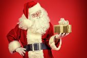 Santa Claus with gift boxes. Over festive red background.