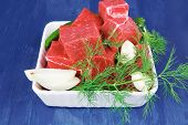 raw fresh beef meat slices in a white bowls with dill and green hot peppers serving over blue wooden table