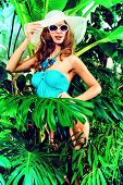 Beautiful young woman in swimsuit stands among the tropical plants. Vacation. Tropics.