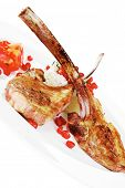 meat savory: roast veal ribs with rice garnish and pomegranate seeds over white background