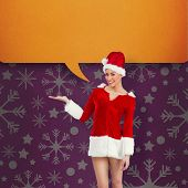 Pretty santa girl presenting with hand against pink vignette