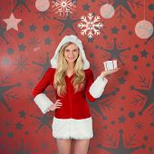Pretty girl in santa outfit holding gift against orange