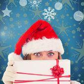 Festive blonde holding a gift against blue vignette