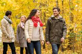 love, relationship, season, friendship and people concept - group of smiling men and women walking in autumn park