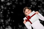 Cute little girl showing card against red christmas ribbon